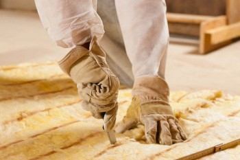 how to weatherize your home, close-up photo of hands cutting insulation