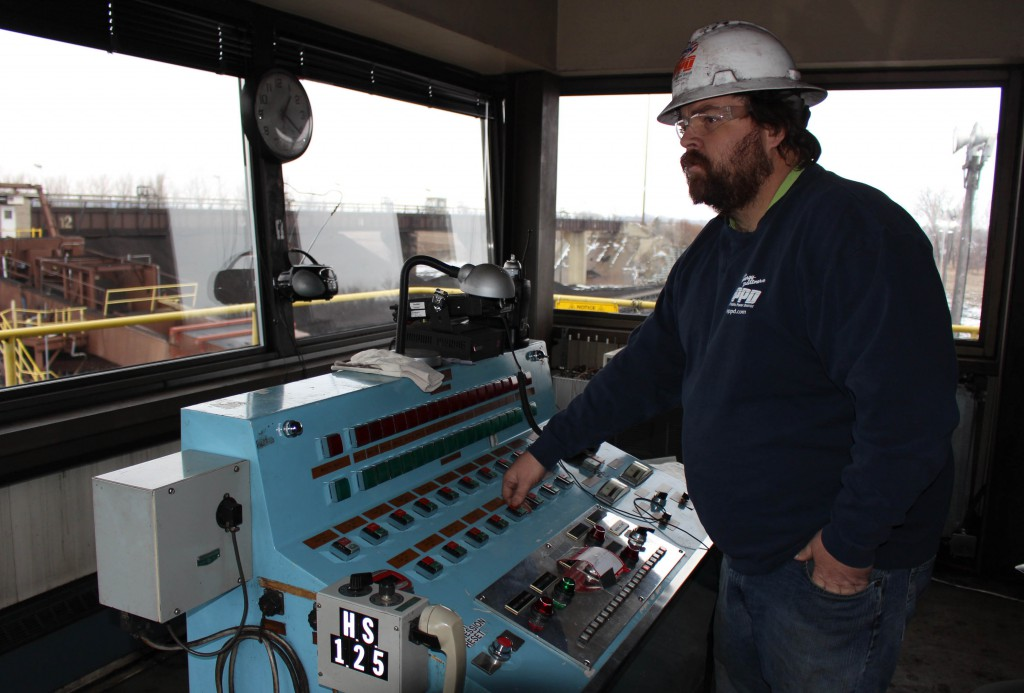 Bill Creek, yard equipment operator first class, demonstrates the switches that open train cars to deliver coal at Nebraska City Station.