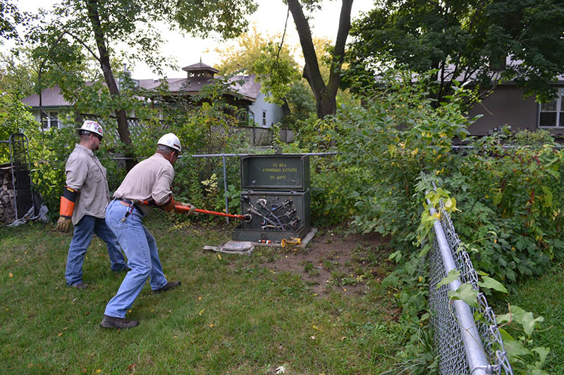 """OPPD crew members repair a padmount transformer using a """"hot stick."""" Proper landscaping around the transformer makes the repair easier."""