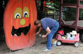 A Vala's Pumpkin Patch employee touches up a cutout prior to the attraction opening on Sept. 16.