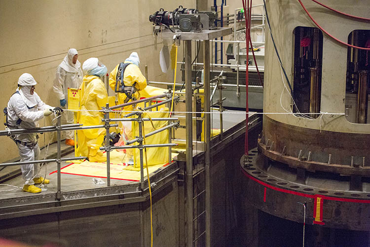 Setting the head: In the FCS containment building, tag-line operators Larry Faris, far left, and Brandon Mickells, in the next photo, help guide the reactor vessel head into position.
