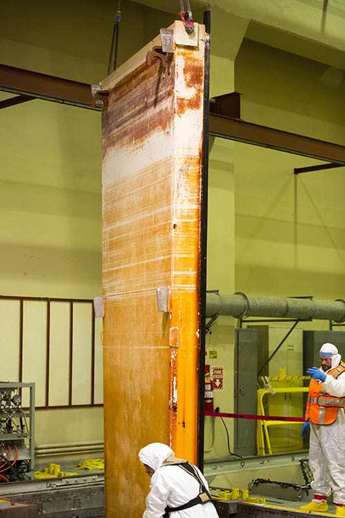 In the auxiliary building, Josh Wheeler, in the orange vest, signals to the crane operator to place the spent-fuel pool sluice gate into position.
