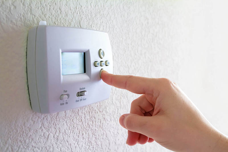 Hand pressing a button on a smart thermostat on a wall