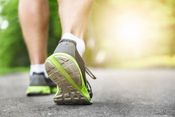 Athlete runner feet running on road.