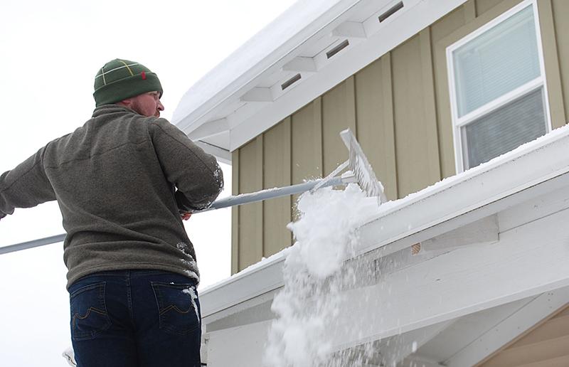 Man using a roof rake in winter.