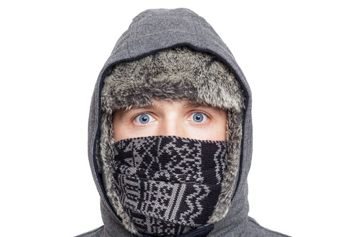 Young man in hat, scarf and hood hiding from the cold weather in