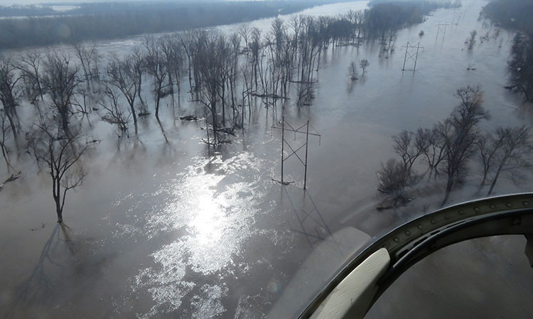 transmission line surrounded by flood waters. Flooding Awareness Month, March 2021