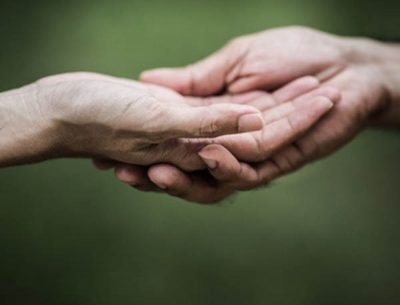 two hands clasped against a green background
