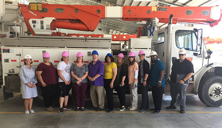 line of educators and tour hosts in front of an OPPD line truck at the utility's Omaha Service Center