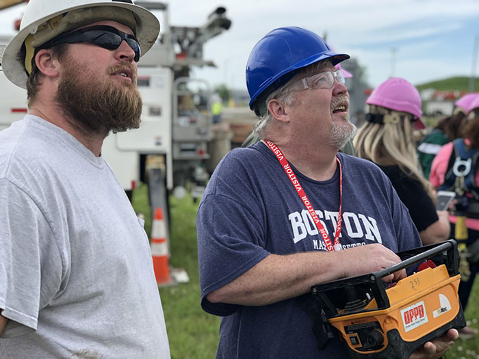 Teacher operates the controls of an auger utility truck as a lineman watches.