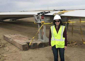 Courtney Kennedy, manager of alternative energy resources for OPPD, standing next to a wind turbine blade