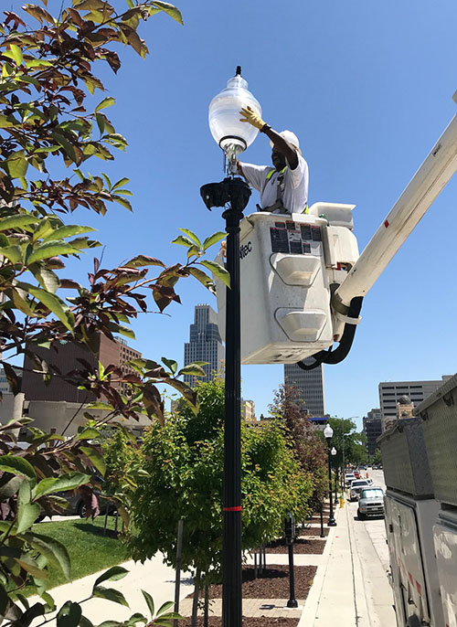 OPPD employee replacing a streetlight fixture in downtown Omaha during College World Series