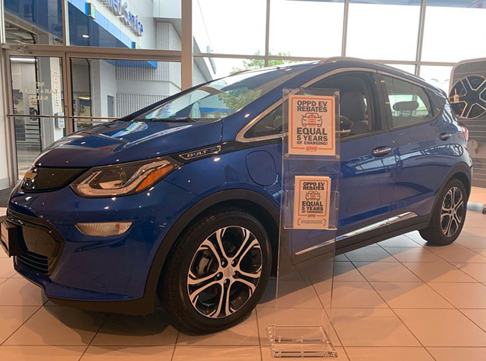 Signage explaining OPPD's EV rebate program sit alongside a Chevy Bolt at a local Omaha dealership.
