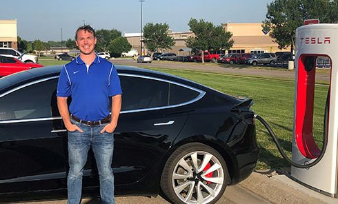 Matt Lentz with his Tesla sedan near a charging station in Omaha.