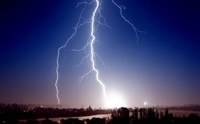 A bolt of lightning goes from cloud to ground from a dark sky.