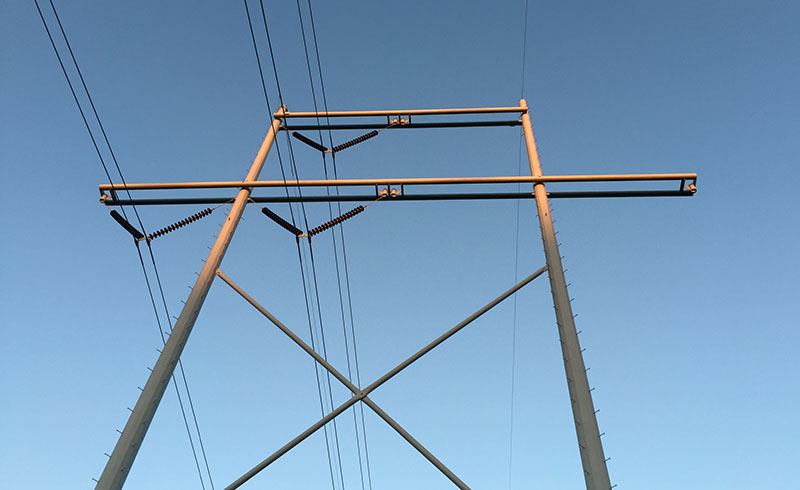 locating transmission lines, a transmission line tower shot from the ground up in perspective