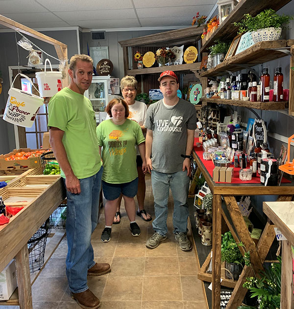 OPPD employee volunteer, Tyler Christensen, left, of OPPD with participants in Roots to Wings inside the organization's store in Arlington, Neb.