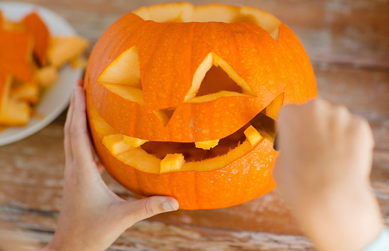 close up of woman with pumpkins at home