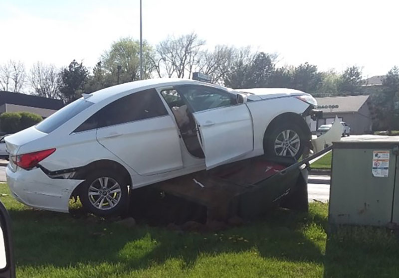 A vehicle sits atop a switchgear box following an accident in Omaha, Nebraska., vehicles causing power outages
