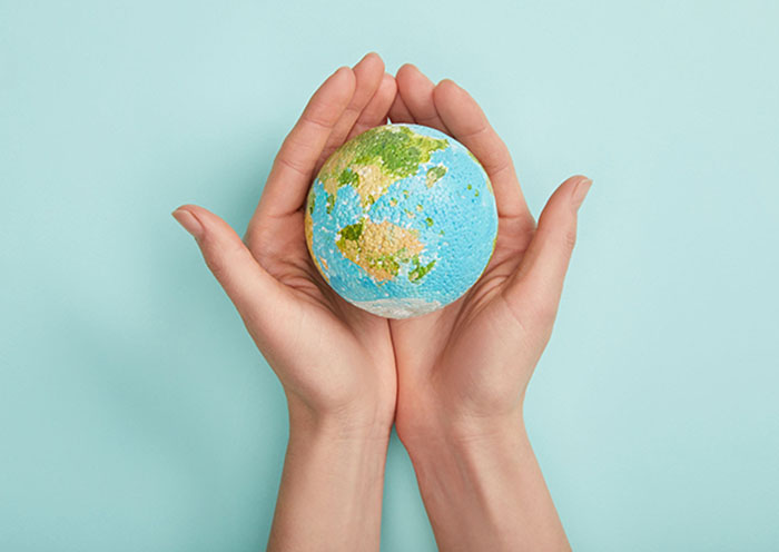 top view of woman holding planet model on turquoise background,
